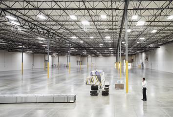 Caucasian businessman standing in empty warehouse