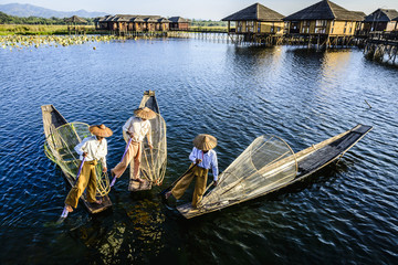 Asian fishermen fishing in canoes on river, Myanmar