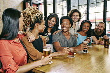 Smiling friends drinking at table in bar
