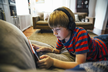 Caucasian boy using digital tablet on sofa