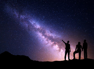 Milky Way with silhouette of a standing young man pointing finger in night starry sky and his parents. Colorful night landscape. Beautiful Universe, travel background with sky full of stars
