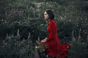 Woman in red dress sitting in meadow among wildflowers