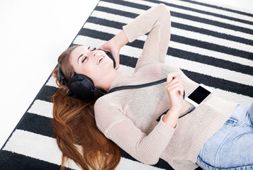 Woman with headphones lying and listening to music at home
