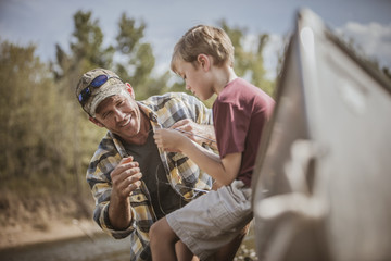 Caucasian father teaching son to tie fishing lures
