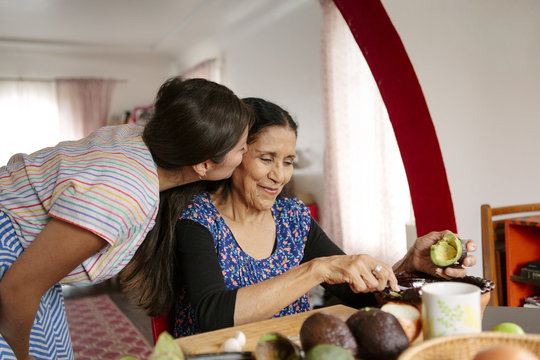 Woman kissing grandmother cooking in kitchen