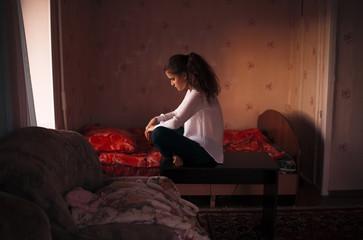 Caucasian woman sitting in bedroom