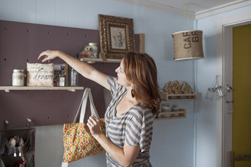 Caucasian business owner arranging items in store