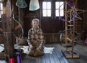 Asian woman sitting near loom