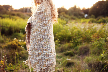 Woman wrapped in blanket walking in field