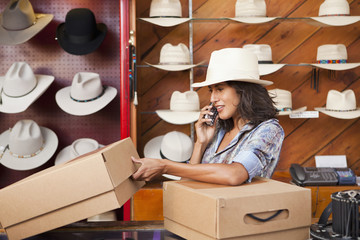 Ecuadorian woman talking on cell phone in hat store