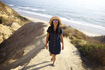 Mixed race woman standing on rock at beach