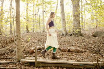 Woman walking on wooden walkway in forest