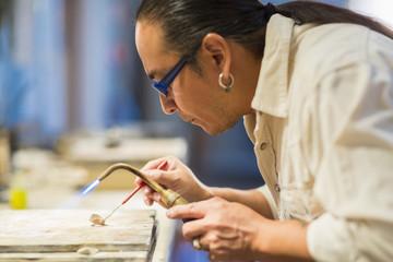 Close up of Native American jeweler using blowtorch in studio