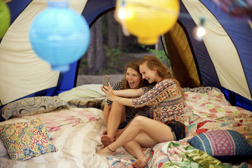 Girls taking selfie with cell phone in camping tent