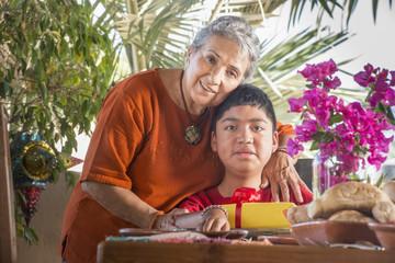 Older Hispanic woman hugging grandson