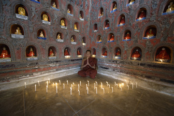 Asian monk-in-training praying in ancient temple