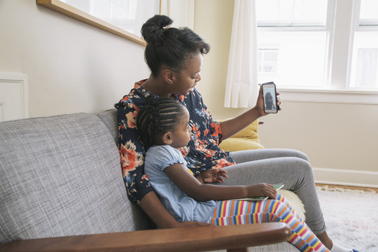 African American mother and daughter video chatting on cell phone