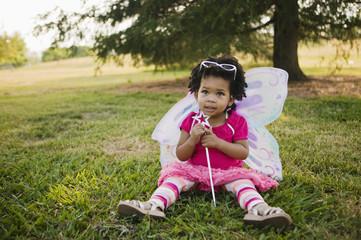 Black baby girl in fairy costume in park Wall mural