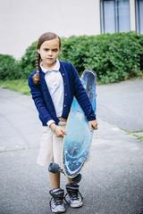 Mixed race girl holding skateboard on sidewalk