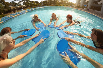 Older Caucasian women playing with boards in swimming pool