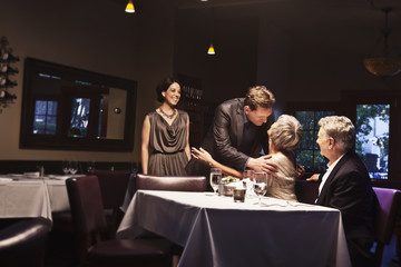 Couple greeting friends in restaurant