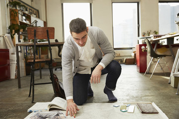 Caucasian businessman working on floor in office