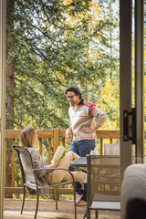 Hispanic couple relaxing on patio beyond doorway