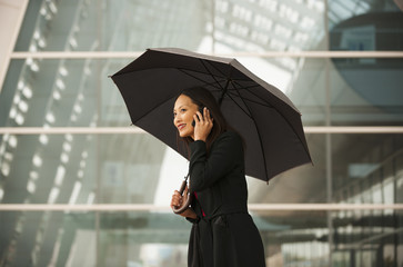 Smiling businesswoman with umbrella talking on cell phone