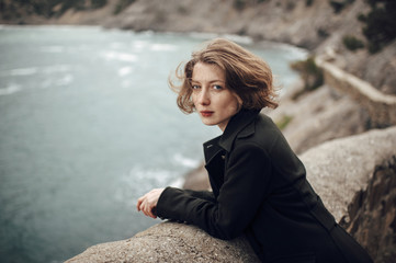 Caucasian woman standing on cliff over coastline
