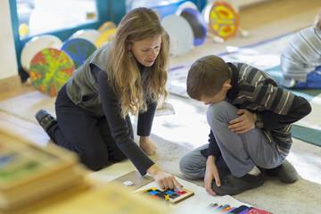 Caucasian Montessori teacher helping student in classroom