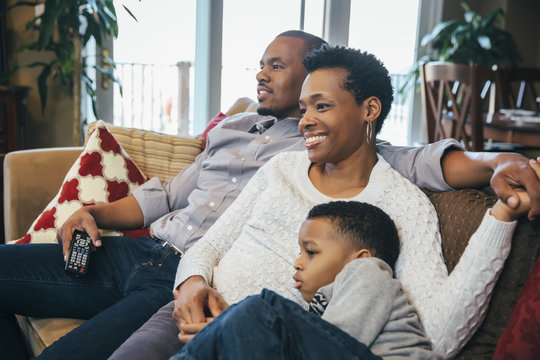 Black family watching television on sofa