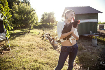 Caucasian farmer holding chicken by hen house