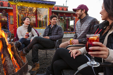 Couples drinking cocktails and beer outdoors at storefront campfire