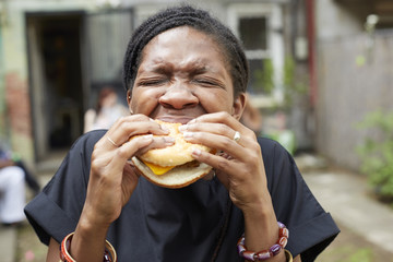 Woman eating hamburger on backyard barbecue