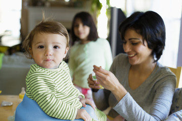 Hispanic mother feeding toddler in kitchen