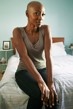 Smiling African American woman sitting on bed