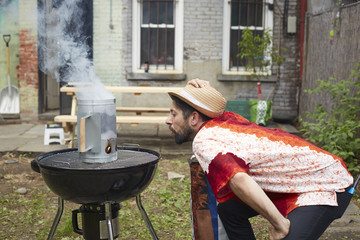 Man lighting charcoal for grill in backyard