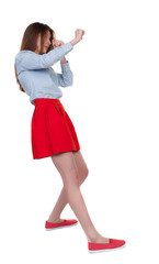 skinny woman funny fights waving his arms and legs. Isolated over white background. Long-haired brunette in red skirt leaned protected from impact.