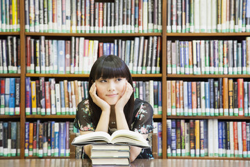 Smiling woman daydreaming in library