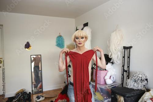 Caucasian drag queen choosing gown in living room