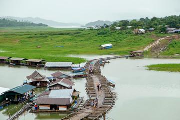 Tourist walking on village antique and wooden bridge traditional culture in dam at sangkhlaburi, kanchanaburi, thailand