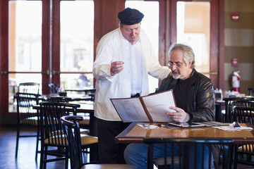 Caucasian man talking to chef in restaurant