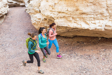 Women running in canyon wearing backpacks