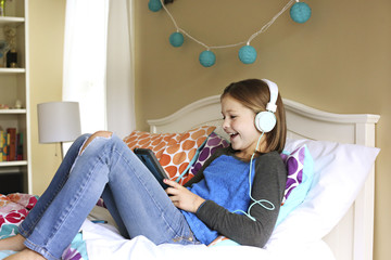 Girl listening to headphones with digital tablet on bed