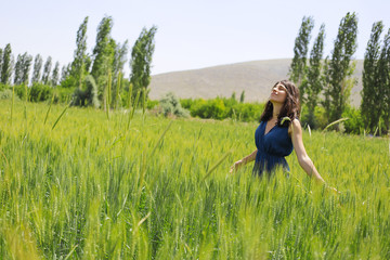 Happy woman in the young green wheat