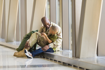 African American soldier and son talking in airport