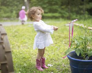 Girl playing with wand in backyard garden