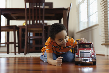 Mixed race boy playing with fire truck on floor