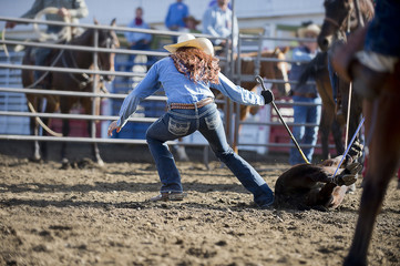 Caucasian cowgirl tying horse in rodeo on ranch