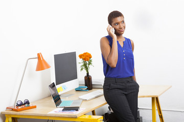 Black businesswoman talking on cell phone at office desk